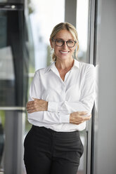 Businesswoman in office leaning against window, with arms crossed - RBF06697