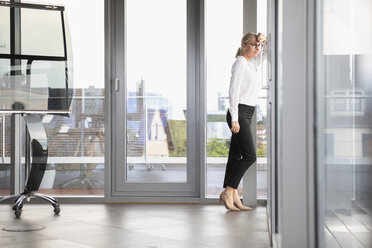Successful businesswoman standing in office, looking out of window - RBF06700