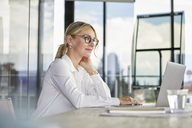 Businesswoman sitting at desk, thinking - RBF06703