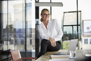 Businesswoman sitting on desk, smiling friendly - RBF06706