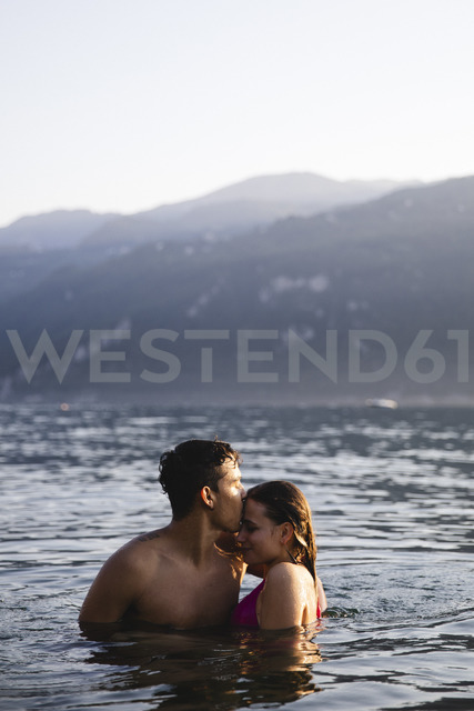 Affectionate young couple kissing in a lake - MRAF00294