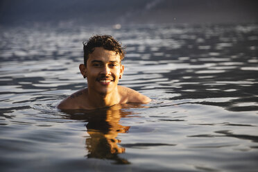 Portrait of smiling young man in a lake - MRAF00300