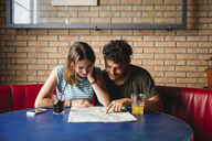 Smiling young couple sitting at table in a cafe with map - MRAF00327