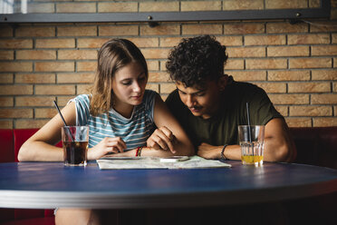 Young couple sitting at table in a cafe with map and cell phone - MRAF00330