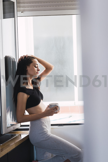 Beautiful young woman with cup of coffee at the window at home - KKAF01817