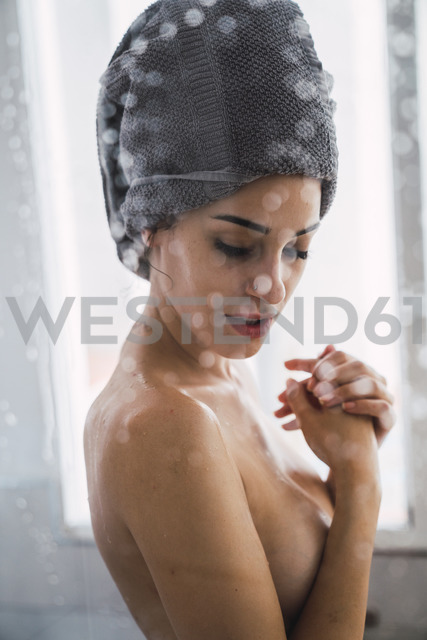 Barechested young woman with towel around her head at home - KKAF01829