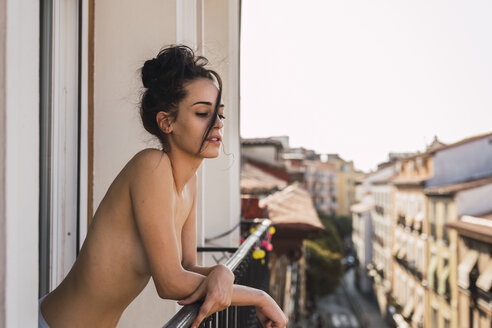 Beautiful barechested young woman on balcony above the city - KKAF01832