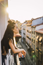 Beautiful young woman on balcony above the city at sunset - KKAF01835