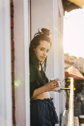 Portrait of beautiful young woman on balcony above the city at sunset with cup of tea - KKAF01838