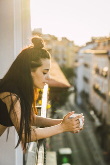 Beautiful young woman on balcony above the city at sunset with cup of coffee - KKAF01841