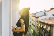 Beautiful young woman on balcony above the city at sunset - KKAF01844