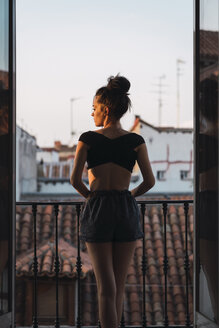 Beautiful young woman standing on balcony at sunset - KKAF01847