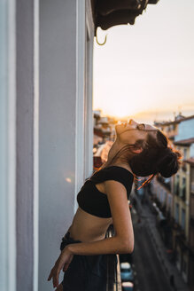 Beautiful young woman on balcony above the city at sunset - KKAF01850