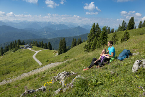 Germany, Bavaria, Brauneck near Lenggries, happy young couple having a break sitting in meadow in alpine landscape - LBF02074