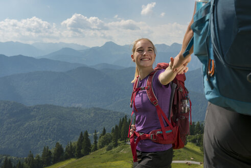 Germany, Bavaria, Brauneck near Lenggries, happy young woman hiking in alpine landscape holding hand of boyfriend - LBF02077