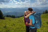 Germany, Bavaria, Brauneck near Lenggries, happy young couple hugging and kissing in alpine landscape - LBF02080