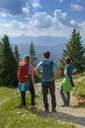 Germany, Bavaria, Brauneck near Lenggries, young friends standing in alpine landscape looking at view - LBF02083