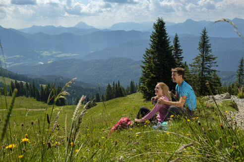 Germany, Bavaria, Brauneck near Lenggries, happy young couple having a break sitting in meadow in alpine landscape - LBF02086