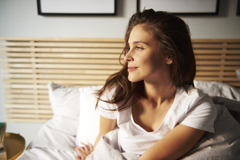 Smiling young woman sitting on bed looking at distance - ABIF01015