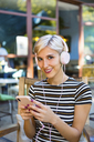 Portrait of smiling young woman with smartphone listening music with headphones at pavement cafe - MGIF00252