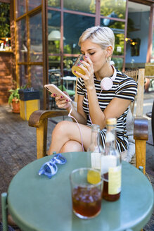 Young woman at pavement cafe enjoying soft drink while looking at smartphone - MGIF00255