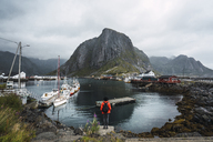 Norway, Lofoten, rear view of man standing at the coast - KKAF01862