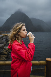 Norway, Lofoten, young woman at the coast drinking from takeaway coffee - KKAF01880