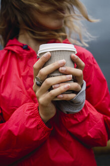 Norway, Lofoten, close-up of young woman at the coast holding takeaway coffee - KKAF01883