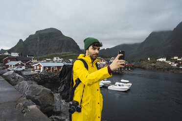 Norway, Lofoten, young man in a fishing village at the coast taking a selfie - KKAF01886