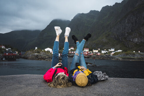 Norway, Lofoten, two young women lying on a pier at the coast - KKAF01889