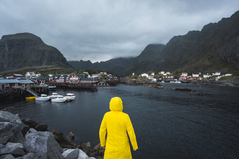 Norway, Lofoten, rear view of man standing in a fishing village at the coast - KKAF01892
