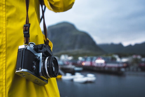 Norway, Lofoten, close-up of man with a camera at a coastal town - KKAF01895