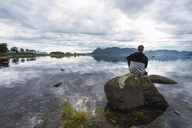 Norway, Senja island, rear view of man sitting on a rock at the coast - KKAF01901