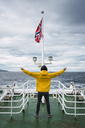 Norway, Senja island, rear view of man standing on ship deck with outstretched arms - KKAF01904