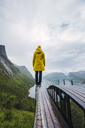 Norway, Senja island, rear view of man standing on an observation deck at the coast - KKAF01910