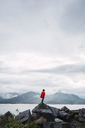 Norway, Senja island, rear view of man standing on a rock at the coast - KKAF01919