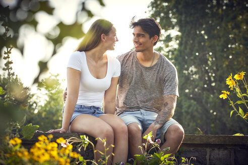 Romantic young couple sitting on wall in a park, with arms around - SRYF00788