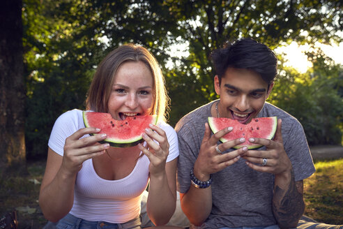 Young couple sitting in park, eating watermelon - SRYF00812