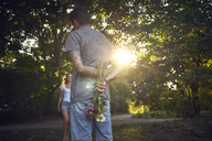 Young man meeting his girlfriend in a park, gifting her with flowers - SRYF00824
