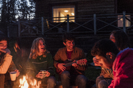 Group of friends sitting at a campfire, talking and playing guitar - KKAF01945