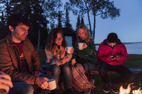Group of friends sitting at a campfire, talking and drinking tea - KKAF01951