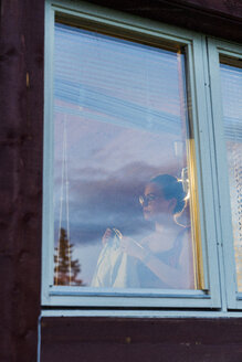 Young woman standing at window, changing clothes - KKAF01963