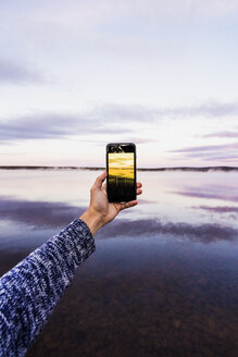 Sweden, Lapland,  Person taking a smartphone picture of the sunset - KKAF01978
