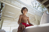 Portrait of serious little boy resting at lounge on the beach - AZOF00034
