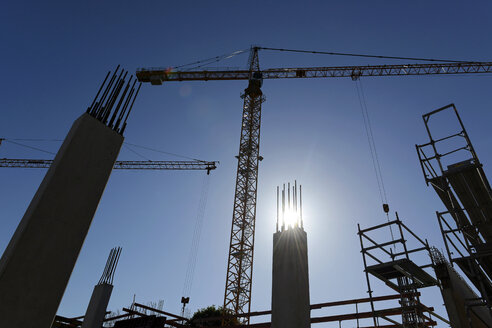 Germany, Bavaria, Geretsried, construction site, crane against the sun - LHF00585