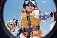 Toddler wearing life jacket and diving goggles with brother in background - AZOF00042