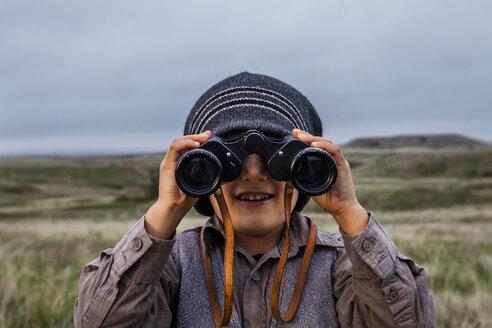 Boy wearing explorer costume holding binoculars - AURF04897