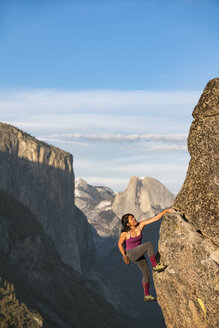 Female Climber Climbing On Rock In Yosemite With El Capitan And Half Dome In Background - AURF05086