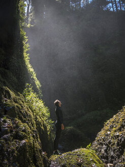 COLUMBIA RIVER GORGE, OREGON, USA. A woman in a wetsuit stands in a dark, fern-lined canyon with sunlight and mist falling from above. - AURF05119
