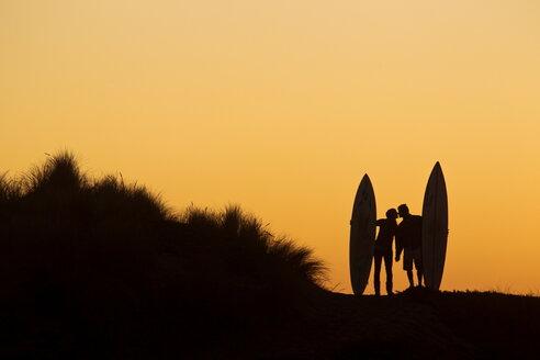 Couple kissing after surf - AURF05146